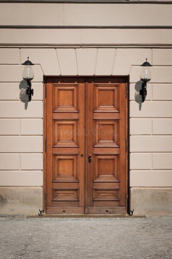 Деревянный вход здания двери на улицу с фонариками на стене стоковое изображение