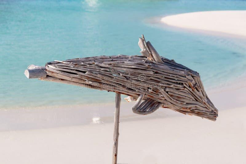 Деревянный дельфин с ясным открытым морем и белым песком как предпосылка стоковая фотография rf