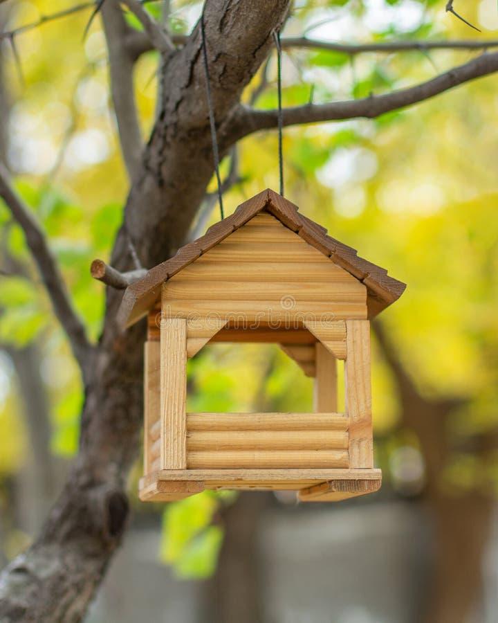 Деревянный дом, висящий на дереве, птицевод Маленький дом для кормления маленьких птиц зимой стоковое фото rf