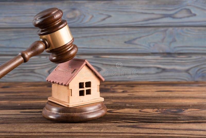Деревянный дом, молоток судьи на деревянной предпосылке стоковые изображения