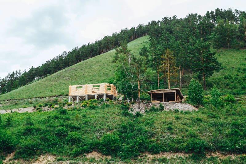 Деревянный дом под конструкцией в горах стоковые изображения