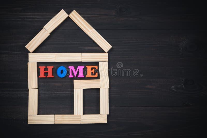 Деревянный дом сделанный из блоков игрушки с ДОМАШНЕЙ надписью на темной деревянной предпосылке скопируйте космос стоковое изображение