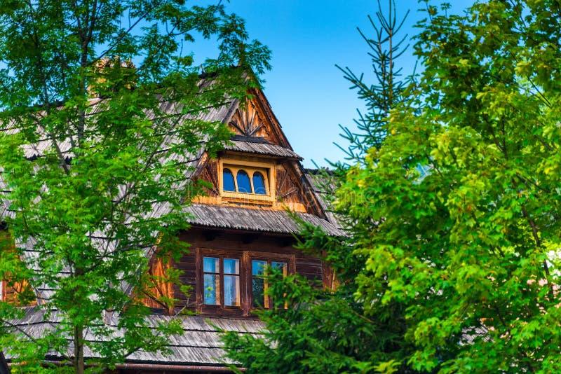 Деревянный дом среди деревьев на солнечный день стоковые фото