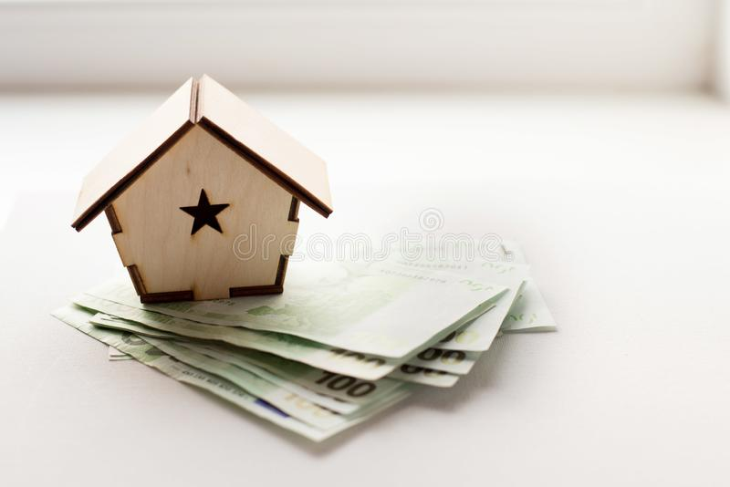деревянный дом стоит на куче бумажного евро счетов как символ ипотеки стоковое изображение rf