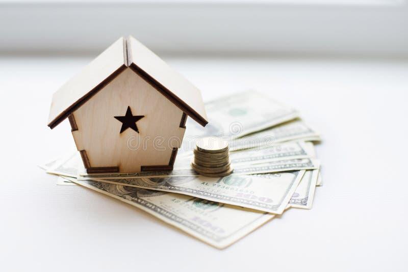 Деревянный дом стоит на куче бумажных долларов счетов как символ ипотеки на белой предпосылке сбережениа дег банка piggy кладя стоковое изображение rf
