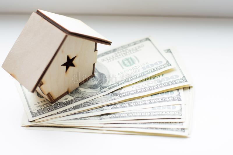 Деревянный дом стоит на куче бумажных долларов счетов как символ ипотеки на белой предпосылке Сохраняя деньги, ипотечный кредит, стоковая фотография rf
