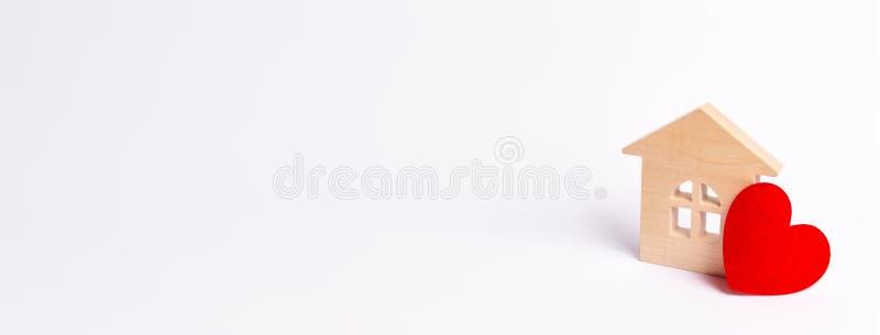Деревянный дом с красным сердцем на белой предпосылке Гнездо влюбленности, отношения влюбленности Покупать дом с молодой семьей д стоковые изображения rf