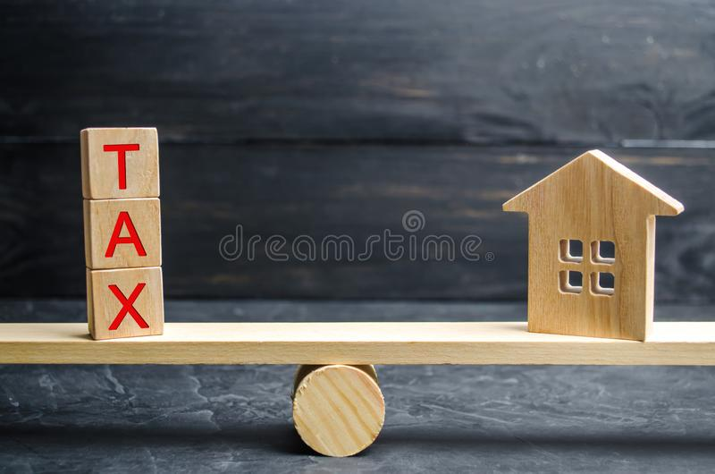 Деревянный дом с ` налога ` надписи на масштабах Налоги на недвижимости, оплате Штраф, недоимки Регистр налогоплательщиков для стоковое фото