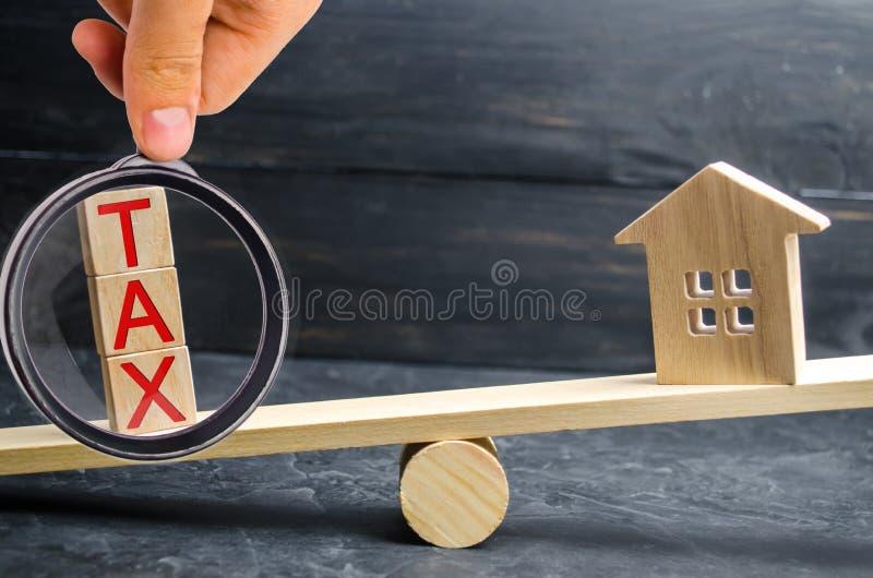 """Деревянный дом с налогом надписи """"в масштабах Налоги на недвижимости, оплате Штраф, недоимки Регистр налогоплательщиков стоковая фотография"""