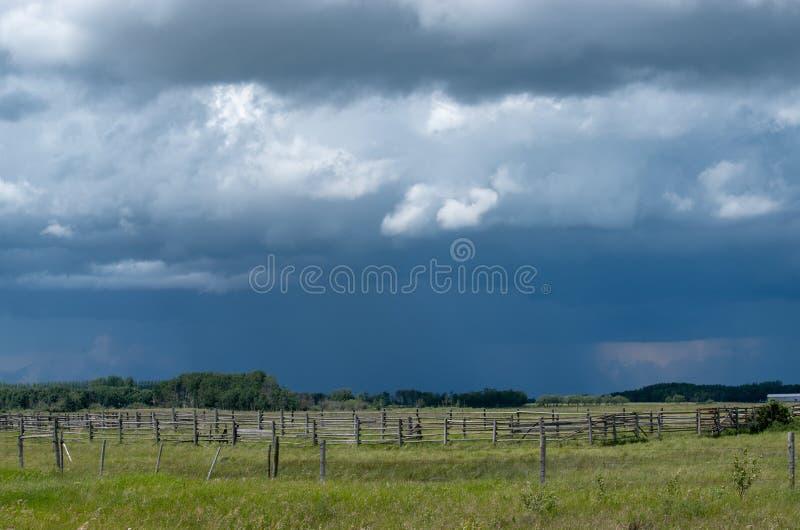Деревянный загон с причаливая облаками шторма, Саскачеван, Канада стоковые фотографии rf