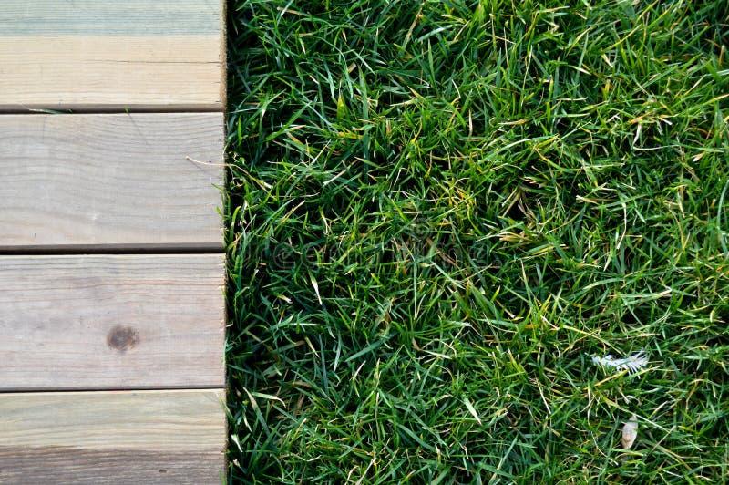 Деревянный идя путь на зеленой траве стоковые изображения
