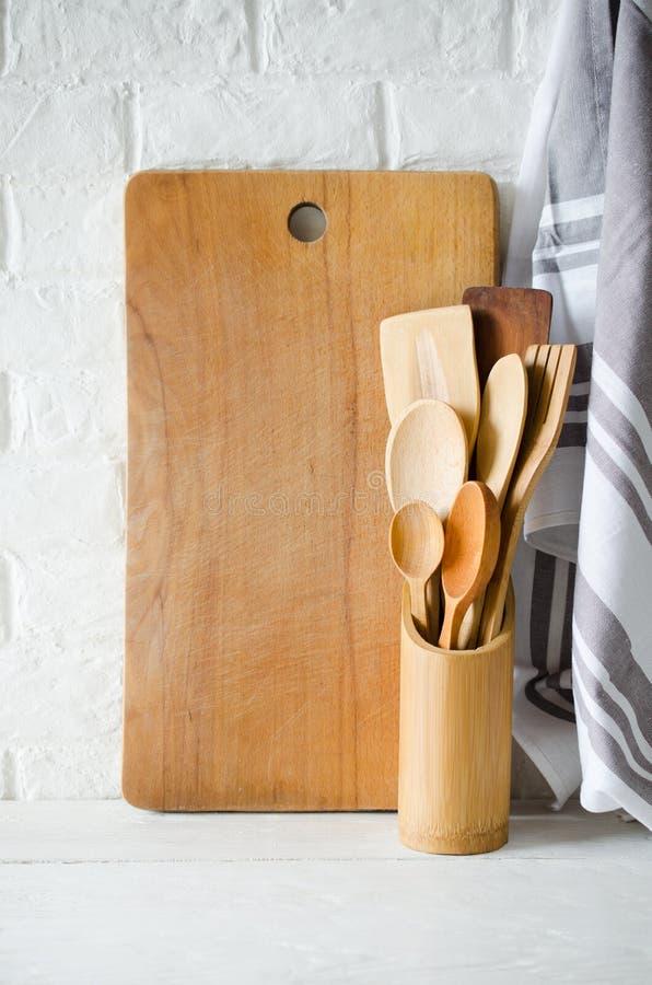 Деревянный или бамбуковый столовый прибор, полотенце и разделочная доска в интерьере белой кухни стоковая фотография rf
