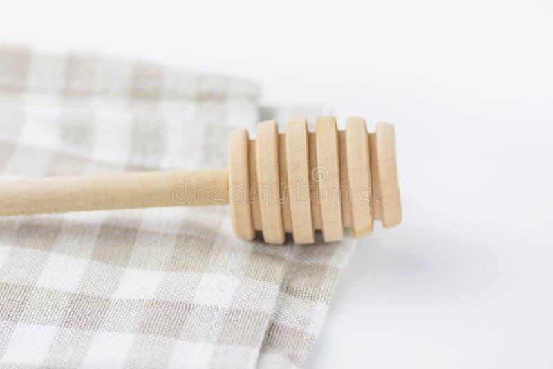 Деревянный ковш меда на белом и бежевом Chequered полотенце кухни хлопка tabletop Предметы первой необходимости выпечки органичес стоковое изображение