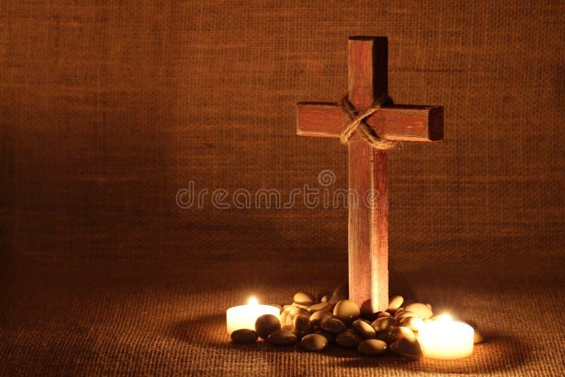 Деревянный крест светом горящей свечи с затрапезной предпосылкой стоковые фотографии rf