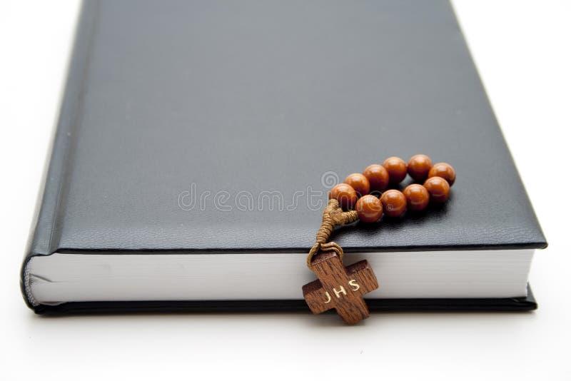 Деревянный крест с цепью на книге стоковая фотография rf