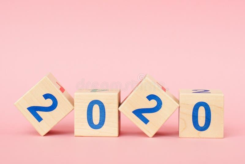Деревянный куб блока с Новым Годом 2020 номера на розовой предпосылке стоковое изображение rf