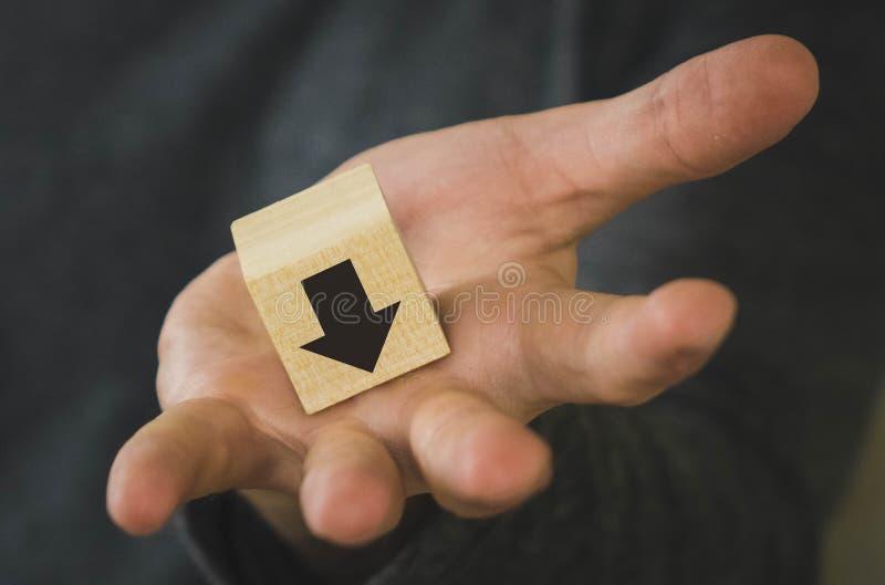 деревянный куб в руке человека с черной стрелкой черноты стрелки значит падение и ухудшение, вымирание, регрессию стоковые изображения