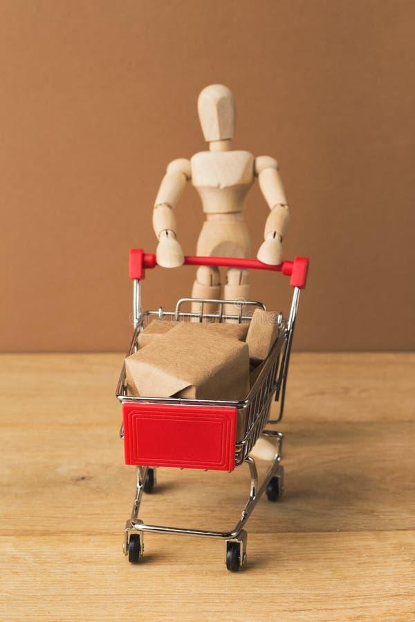 Деревянный манекен с миниатюрной магазинной тележкаой стоковое изображение rf