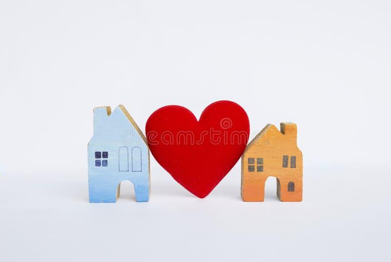 Деревянный миниатюрный дом с красным изолятом сердца на белой предпосылке стоковое фото