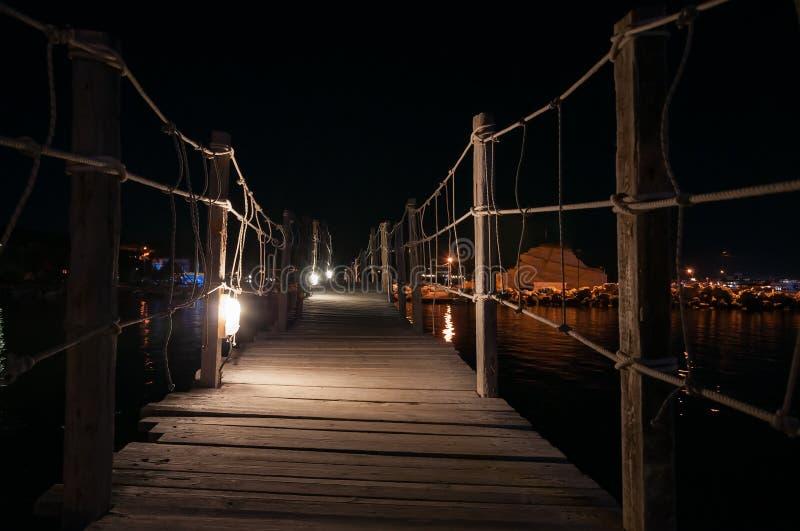 Деревянный мост к острову камеи на ноче стоковые фотографии rf
