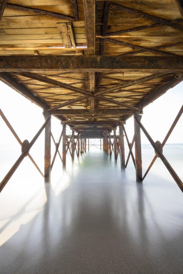 Деревянный мост над океаном на пляже Kassandra, низкой точке зрения с запачканными волнами или воде Alanya, Турция dng стоковое фото