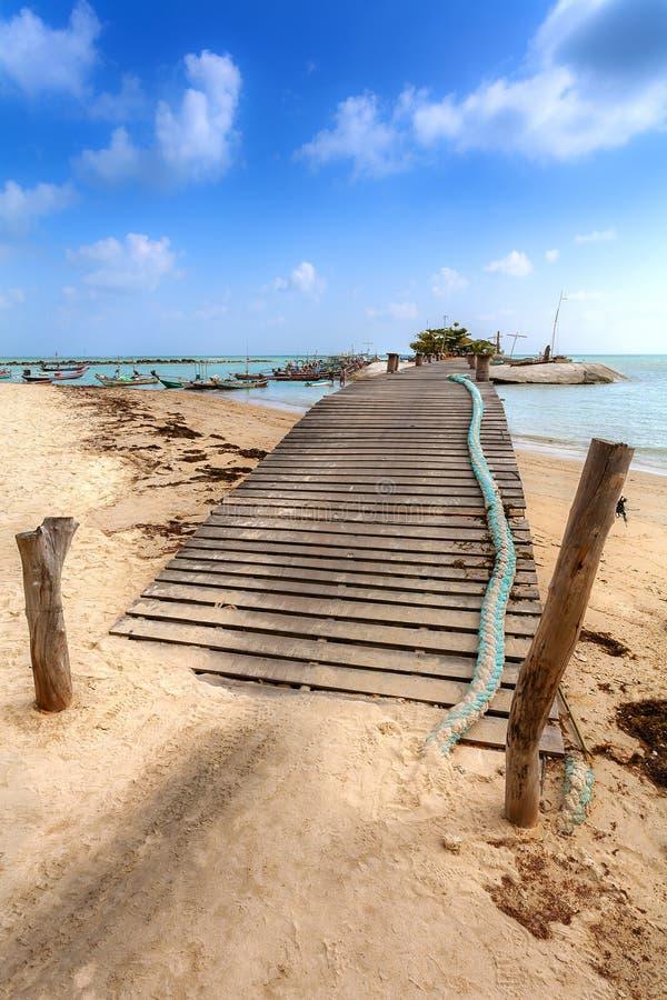 Деревянный мост на пляже с рыбацкими лодками, море с turquois стоковая фотография