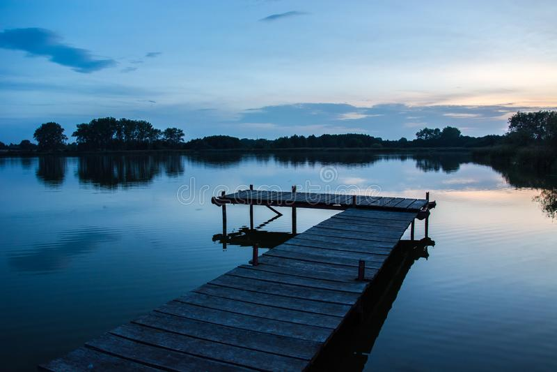 Деревянный мост на спокойном озере, деревья на горизонте стоковая фотография rf