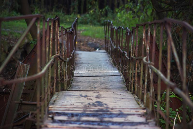 Деревянный мост с ржавым поручнем металла в парке, пути внутри к древесине стоковое фото