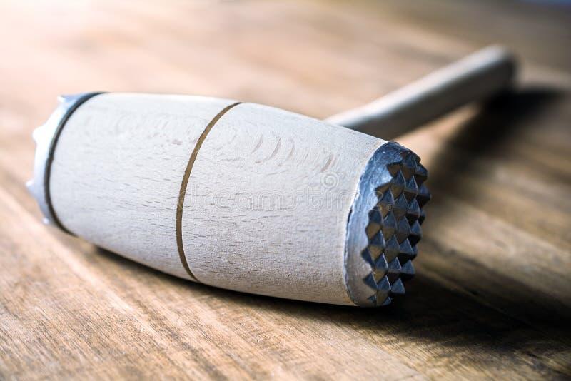 Деревянный мушкел мяса лежа вниз на таблице стоковая фотография