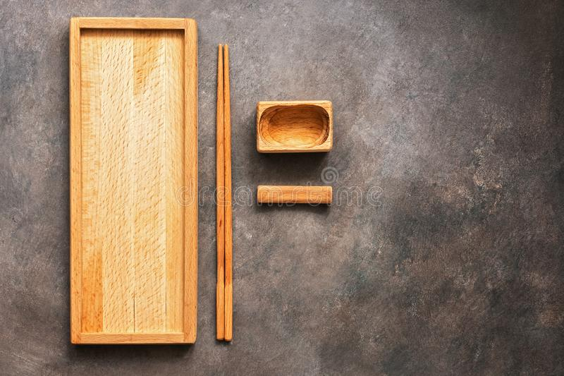 Деревянный набор блюд и суш и кренов кухни столового прибора азиатских, прямоугольной плиты, палочек и шара для соевого соуса на  стоковая фотография
