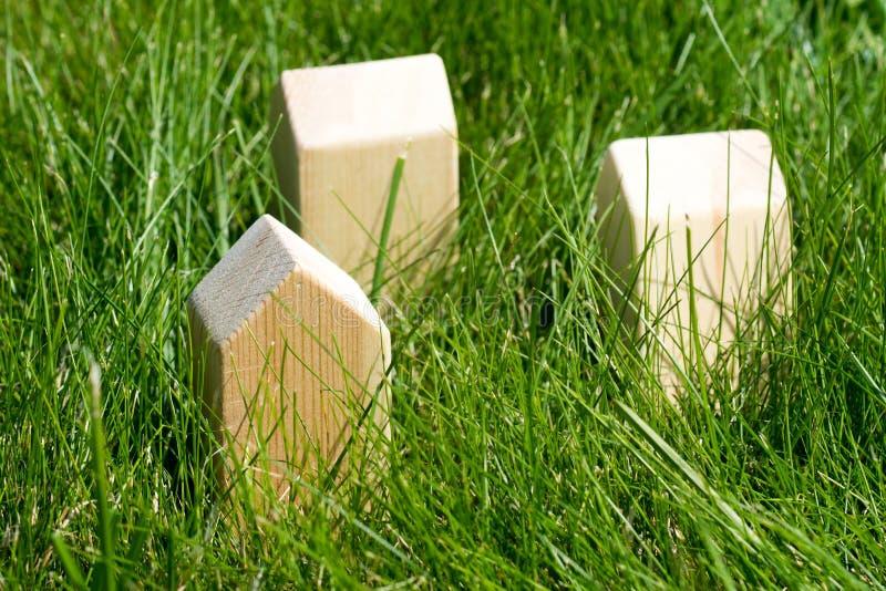 Деревянный дом игрушки 3 на зеленой траве стоковая фотография rf