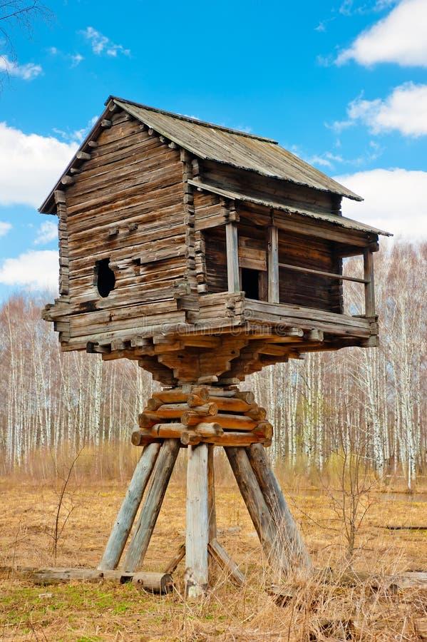 Деревянный дом на поляках в поле стоковое изображение
