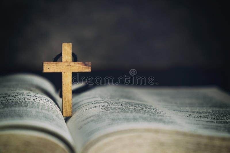 Деревянный перекрестный символ знака и молить к богу с библией в преданности утра стоковые изображения rf