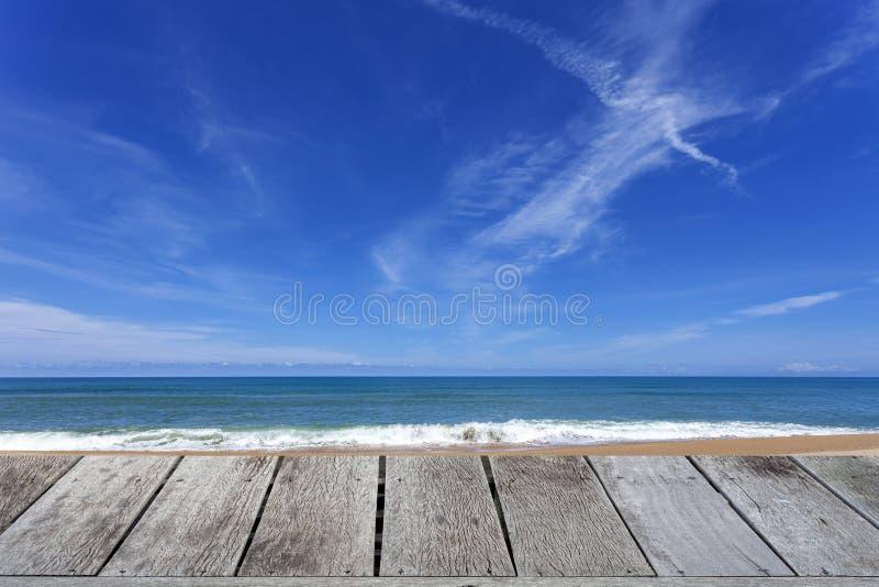 Деревянный пол с красивым голубым небом над тропическим пейзажем песчаного пляжа для предпосылки стоковые фотографии rf