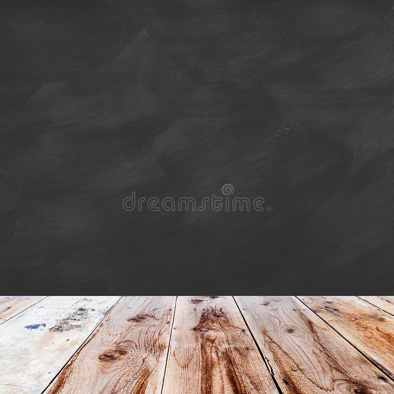 Деревянный пол и черный пробел доски мела стоковое фото
