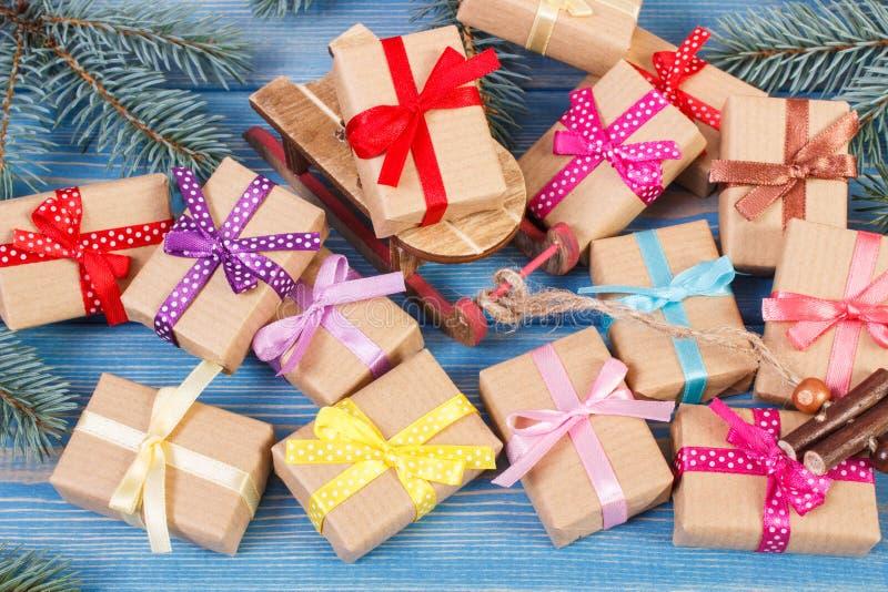 Деревянный скелетон и обернутые подарки с красочными лентами для рождества, елевыми ветвями стоковое фото rf