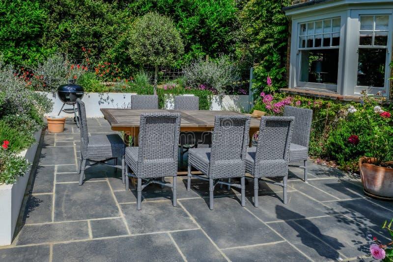 Деревянный стол и серые плетеные стулья на современном патио с круглой Адвокатурой-b-que на заднем плане стоковое изображение rf