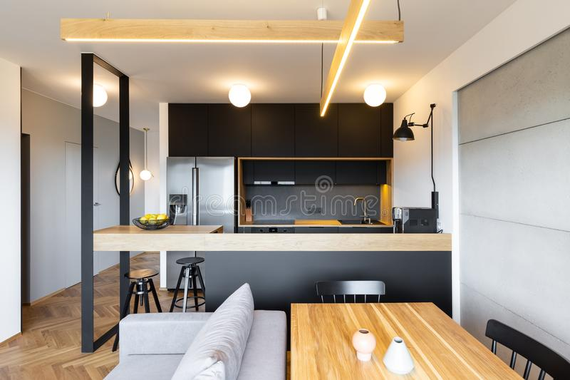 Деревянный стол и стильная мебель кухни в современном, открытом курорте стоковое изображение rf