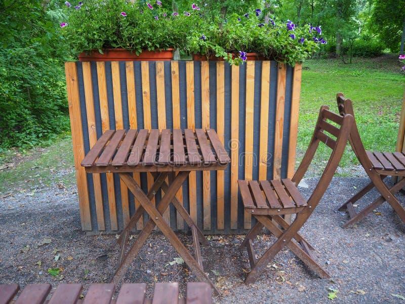 Деревянный стол и стулья на террасе кафа лета улицы в парке стоковая фотография rf