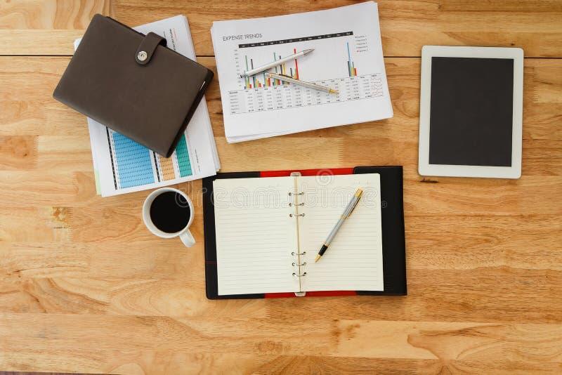 Деревянный стол офиса с канцелярские товарами и кофейной чашкой стоковые изображения rf