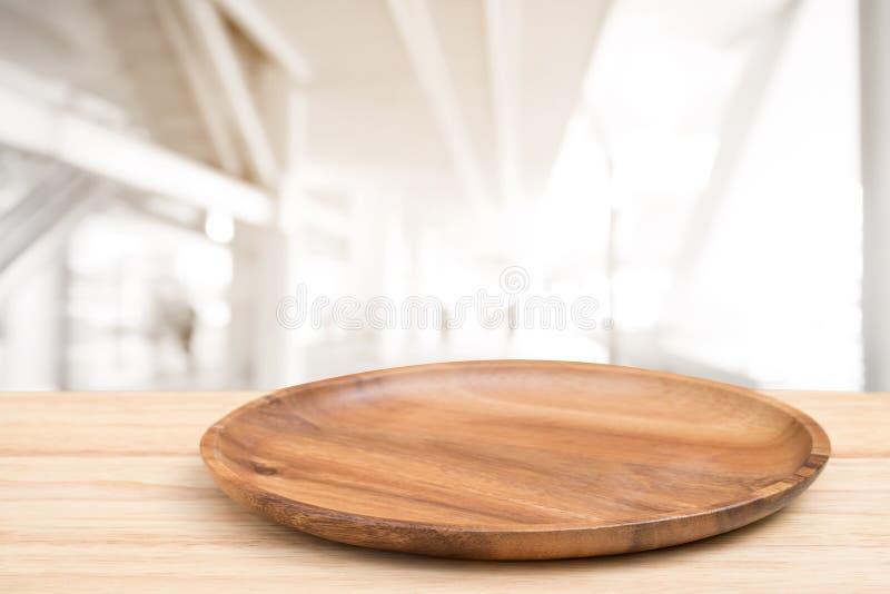 Деревянный стол перспективы и деревянный поднос на верхней части над предпосылкой торгового центра нерезкости, могут быть использ стоковые фотографии rf