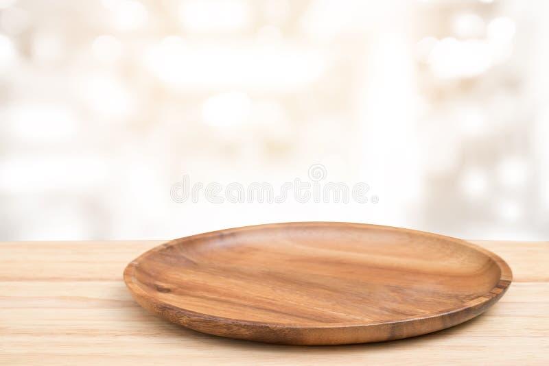 Деревянный стол перспективы и деревянный поднос на верхней части над предпосылкой света bokeh нерезкости, могут быть используемое стоковые фотографии rf