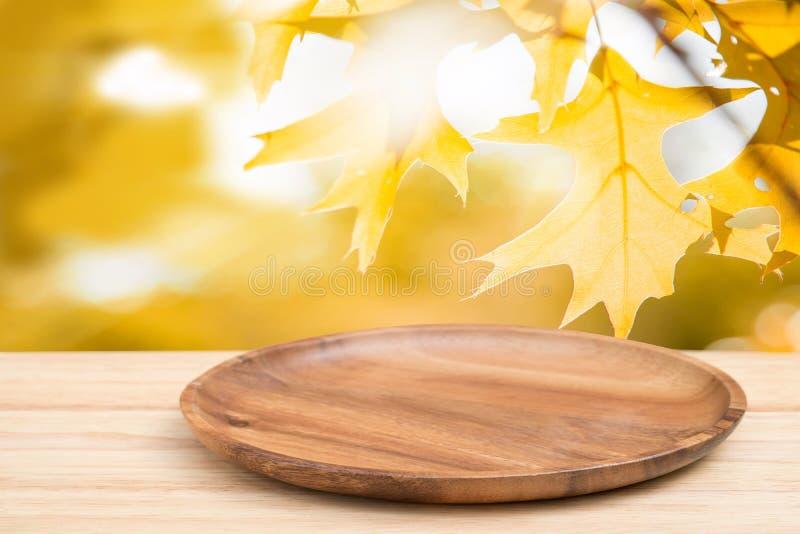 Деревянный стол перспективы на верхней части над нерезкостью естественной кленового листа стоковые фотографии rf