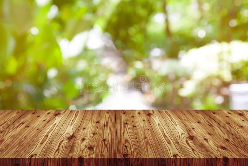 Деревянный стол перспективы на верхней части над предпосылкой нерезкости естественной, может быть используемое насмешливым вверх  стоковые фото