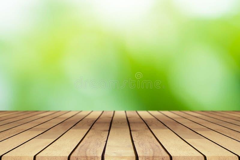 Деревянный стол перспективы на верхней части над предпосылкой нерезкости естественной, ca стоковая фотография rf