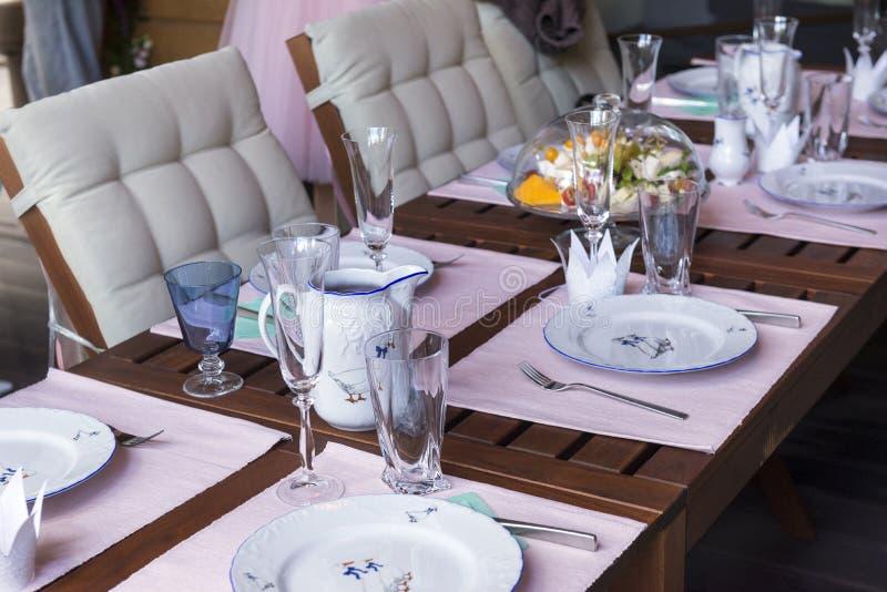 Деревянный стол служил с салфетками, плитами, стеклами, столовым прибором, glas стоковые изображения