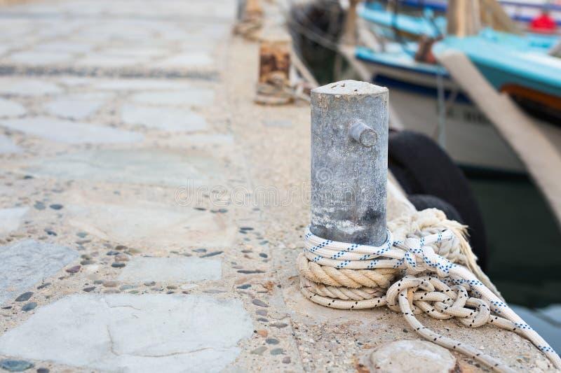 Деревянный столб с зачаливанием ropes для связывать шлюпки и корабли стоковая фотография rf