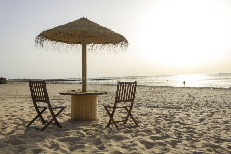 Деревянный стол и стулья с зонтиком на пляже стоковые изображения rf
