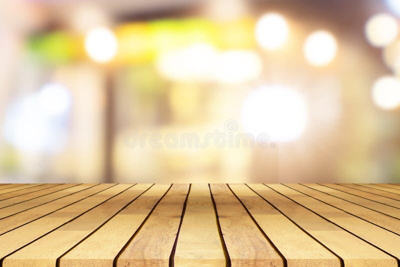 Деревянный стол перспективы на верхней части над предпосылкой кофейни нерезкости стоковые изображения