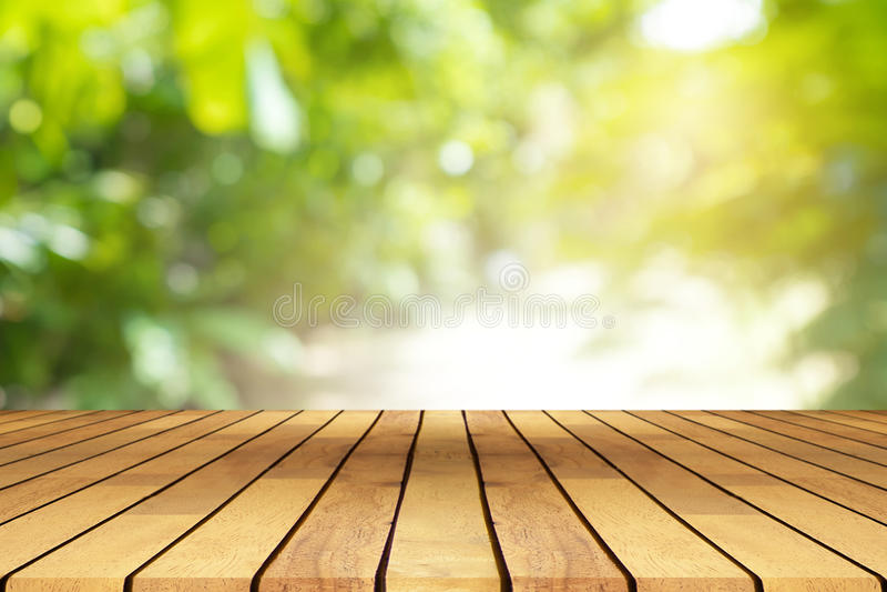 Деревянный стол перспективы на верхней части над предпосылкой нерезкости естественной, ca стоковое изображение rf